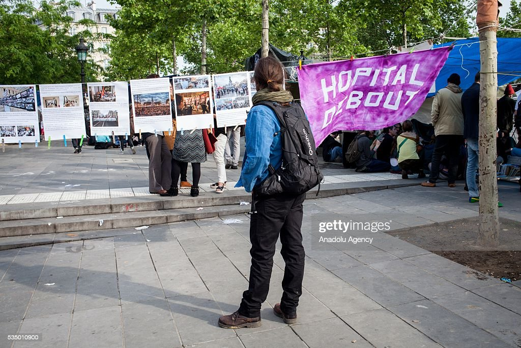 A man walks around Place the Republique and read some banners during the Global Debout meeting 'Nuit Debout' ('The Night awake' or Up all night') in Paris, France on May 28, 2016.