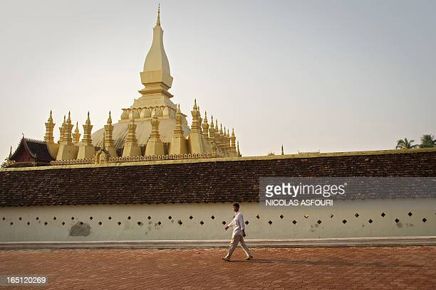 A man walks around the That Luang Stupa in Vientiane the capital of Laos on April 12 2012 ahead of the visit by former Thai prime minister Thaksin...