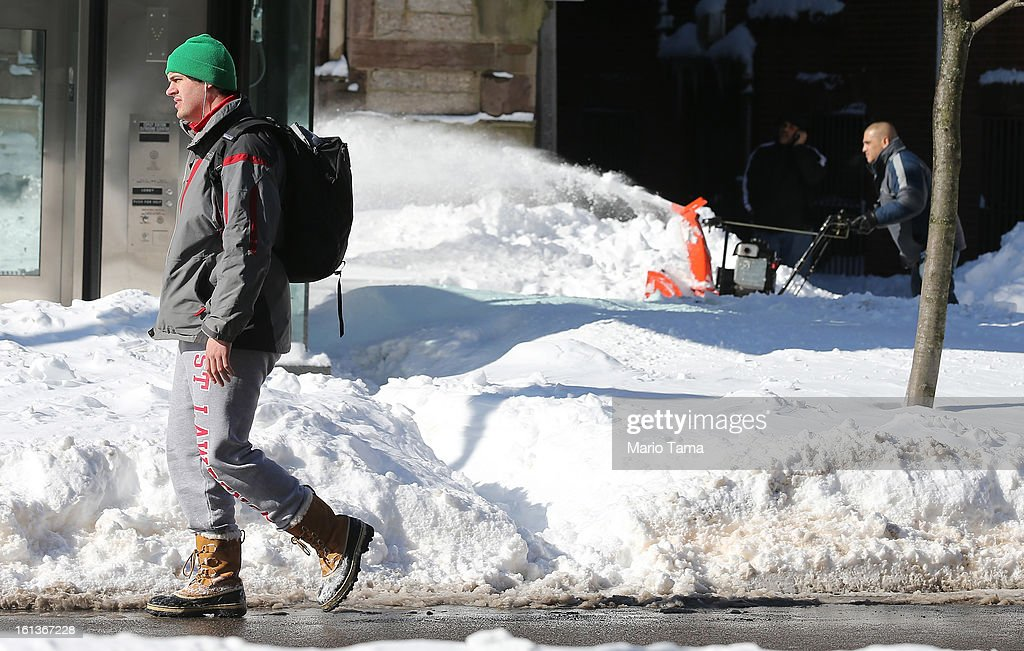 A man walks as another clears snow from a sidewalk in the Back Bay neighborhood following a powerful blizzard on February 10, 2013 in Boston, Massachusetts. The storm dumped more than two feet of snow in parts of New England and more than 200,000 Massachusetts customers remain without power.