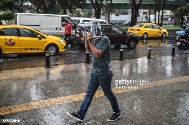 A man walks as he cover his head from the rain with a newspaper on August 22 2017 during a heavy rain at Aksaray district in Istanbul / AFP PHOTO /...