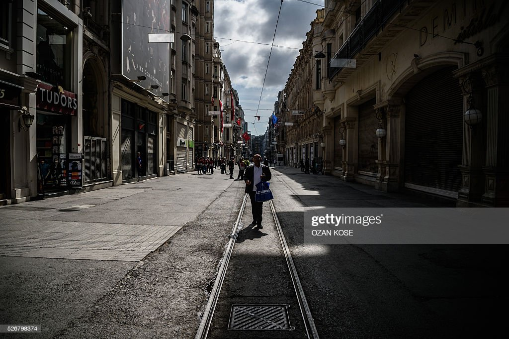 A man walks as Turkish police officers patrol on Istiklal avenue during a May Day rally in Istanbul, on May 1, 2016. Turkish labour activists and leftists marked the annual May Day holiday, with thousands of security deployed and bracing for trouble after the authorities refused to allow protests in central Taksim Square. / AFP / OZAN