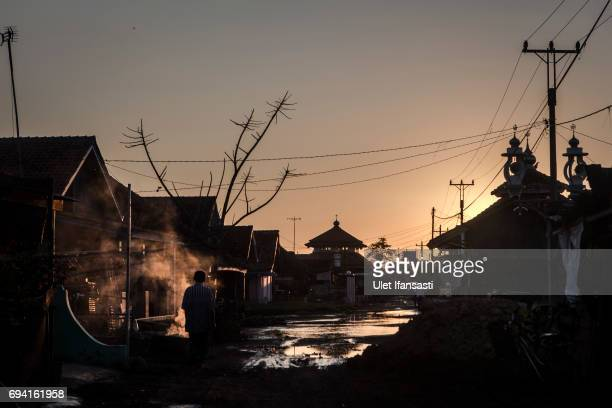 A man walks at a village sits surrounded by rising sea levels on June 6 2017 in Pekalongan Indonesia Indonesia is known to be one of the largest...