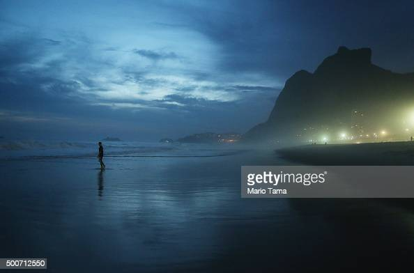 A man walks at dusk along Sao Conrado beach on December 9 2015 in Rio de Janeiro Brazil The city is set to host the Rio 2016 Olympic Games next summer