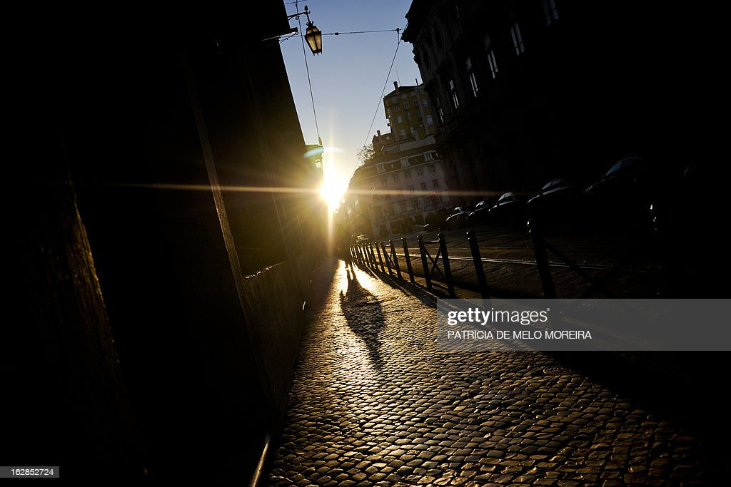 A man walks at Terreiro do Paco in Lisbon during a sunny day on February 28, 2013.