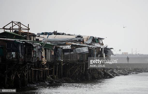 A man walks at the breakwater in Baseco Manila on December 26 2016 Typhoon NockTen which made landfall on the eastern island province of Catanduanes...