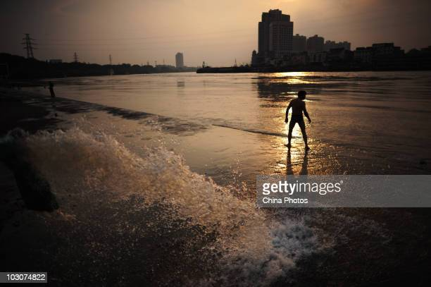 A man walks at the flooded river bank of Longwangmiao water area where the Hanjiang River merges into the Yangtze River on July 24 2010 in Wuhan of...