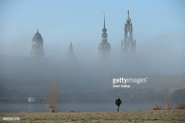 A man walks away from fog rising from the Elbe River shrouding landmarks in the city center including towers of the Residenzschloss Dresden palace...