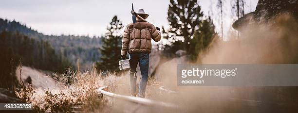 Man walks away on overgrown rustic railroad tracks carrying pickaxe