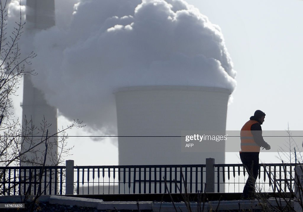 A man walks before a power plant in Beijing on December 5, 2012. Manufacturing activity in China hit a 13-month high in November, HSBC said on December 3, in another sign that the world's second largest economy is emerging from a drawn-out slumber. AFP PHOTO/WANG ZHAO