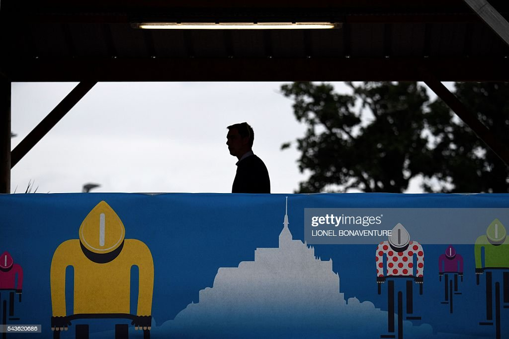 A man walks behind a banner bearing drawings representing Le Mont-Saint-Michel and cyclists wearing colors of the Tour de France's colors of jerseys, at the Equestrian Centre in Saint-Lo, Normandy, on June 29, 2016, three days before the start of the 103rd edition of the Tour de France cycling race. The 2016 Tour de France will start on July 2 in the streets of Le Mont-Saint-Michel and ends on July 24, 2016 down the Champs-Elysees in Paris. / AFP / LIONEL