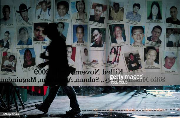 A man walks behind a tarpaulin displaying the names and pictures of 'Maguindanao Massacre' victims during a ceremony marking the 1000th day since the...