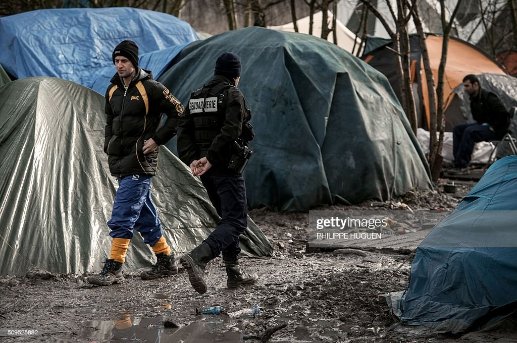 A man walks beside a French gendarme in the so-called 'Jungle' migrant camp in Gande-Synthe where 2,500 refugees from Kurdistan, Iraq and Syria live on February 11, 2016 in Grande-Synthe near the city of Dunkirk, northern France. / AFP / PHILIPPE HUGUEN