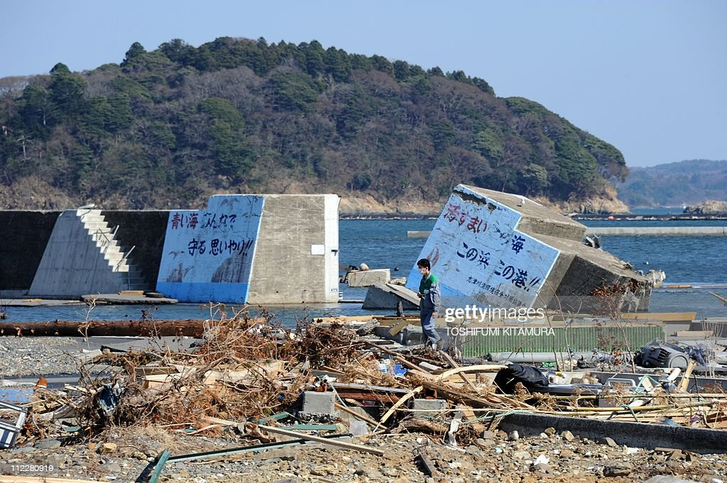 A man walks beside a tsunami destroyed breakwater at the new Shizukawa fishing port in Minamisanriku town, Miyagi prefecture on April 17, 2011. The operator of Japan's tsunami-hit nuclear plant said it aims to reduce radiation leaks within three months and to achieve a 'cold shutdown' within six to nine months. Japan's embattled Tokyo Electric Power Co (TEPCO) offered the timeline in a press conference more than five weeks after a giant quake and tsunami knocked out cooling systems at its six-reactor Fukushima nuclear power station.