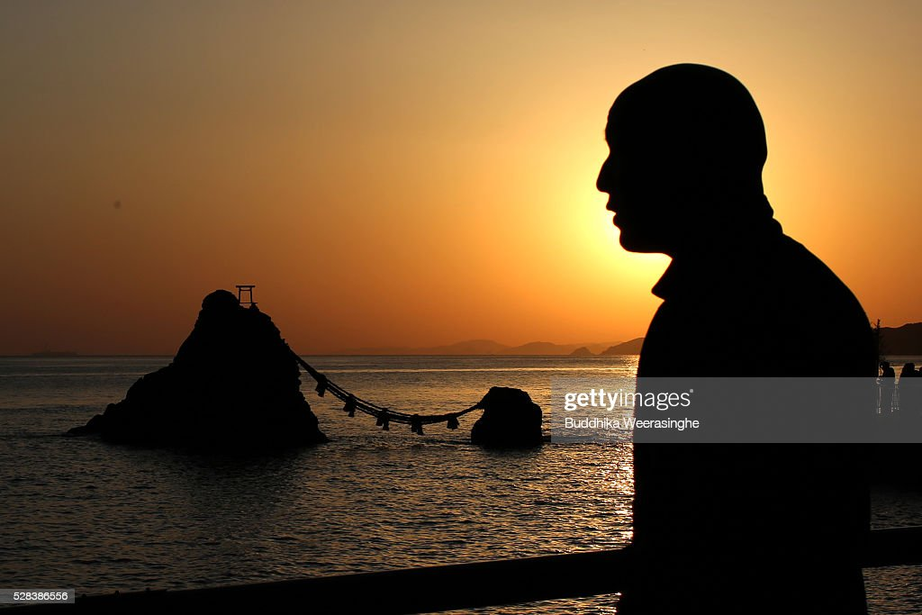 A man walks beside the 'Meoto-Iwa' or couple rocks while sun rise between the 'Meoto-Iwa' or couple rocks and over the sea ahead of the Oshimenawahari ceremony at Futami Okitama Shrine on May 5, 2016 in Ise, Japan. The Oshimenawahari ceremony is held three times a year to exchange the 35 meters long heavy rope made of rice straw that connects the sacred Couple Rock - one small, one big. The Couple Rock serves as a gate to the Okitama Shrine, dedicated to the god Sarutahiko and goddess Ukanomitama from Japanese myth.