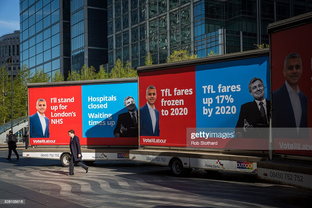 A man walks between campaign adverts for Labour's London Mayoral candidate Sadiq Khan and member of Parliament for Tooting in Montgomery Square in Canary Wharf on May 4, 2016 in London, England. Londoners will go to the polls tomorrow to vote for Mayor Of London with Labour's candidate expected to beat Conservative Party rival Zac Goldsmith to the position.