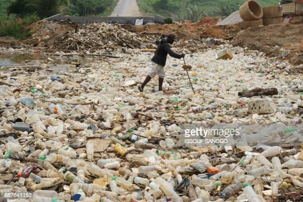A man walks between plastics bottles in a river near Abidjan in Ivory Coast on May 23 2017 / AFP PHOTO / ISSOUF SANOGO