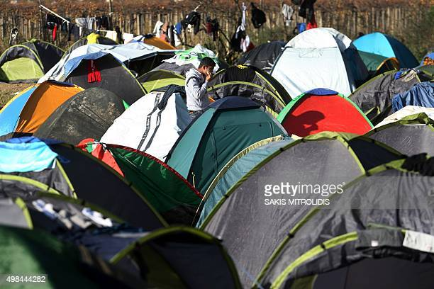A man walks between tents as migrants and refugees wait to cross the border of Greece and Macedonia near Idomeni on November 23 2015 Serbia and...