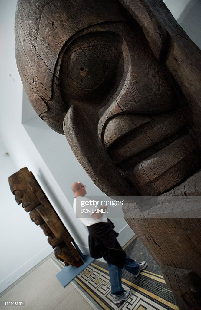 A man walks between two house posts, owned by the Heiltsuk eagle clan of Yálátli (Goose Island), which are on display at the 'Life, Death, and Transformation in the Americas' exhibit at the Brooklyn Museum February 28, 2013 in New York. Themes of life, death, fertility, and regeneration are explored through pre-Columbian and historical artworks, including many pieces that are rarely on display.