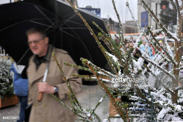 A man walks beyond a Christmas tree with fake snow adorning it in the Christmas Wonderland market under a large umbrella as wet weather sweeps across...