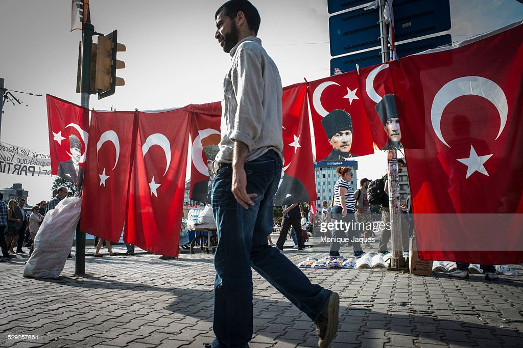 A man walks buy flags picturing the face of Ataturk the founder of Modern Day Turkey Protests began as a fight to save Gezi Park in central Istanbul...