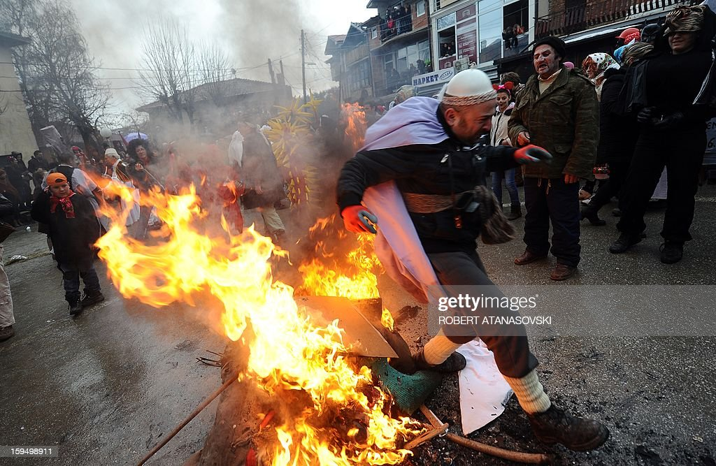 A man walks by a big open fire in the middle of the village of Vevchani, some 170 km from the capital of Skopje, for the traditional mask burning in the late afternoon on the second day of a carnival marking the Orthodox Saint Basil Day, on January 14, 2013.The Vevchani carnival is 1.400 years old and is held every year on the eve of the feast of Saint Basil (14 January), which also marks the beginning of the New Year according to the Julian calendar, observed by the Macedonian Orthodox Church.