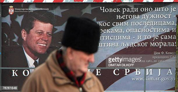 A man walks by a billboard part of a campaign by Serbia's Ministry for Kosovo reading Kosovo is Serbia and showing late US President John Fitzgerald...