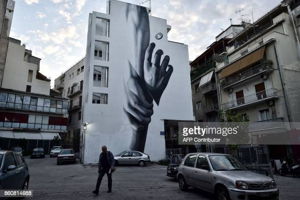 A man walks by a building featuring a mural by graffiti artist INO in central Athens on October 11 2017 An ongoing exhibition devoted to 'Artists in...