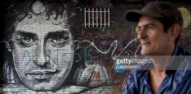 A man walks by a graffiti depicting Argentine musician Gustavo Cerati in Cali Colombia on September 4 2014 Cerati one of the greatest stars of the...