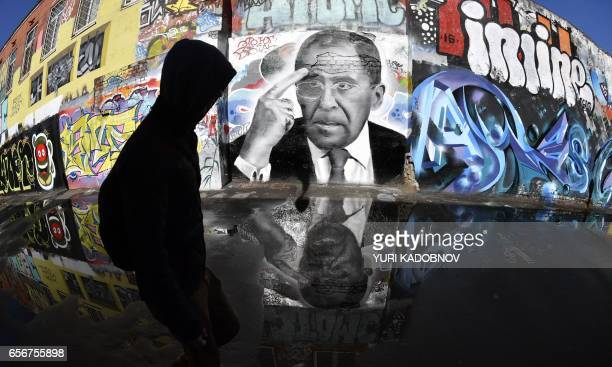 TOPSHOT A man walks by a graffiti depicting Russian Foreign Minister Sergei Lavrov in Moscow on March 23 2017 / AFP PHOTO / Yuri KADOBNOV