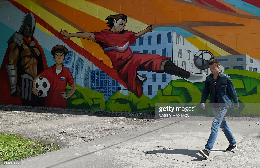 A man walks by a mural allusive to the FIFA 2018 World Cup, on the wall of a building, in Moscow, on May 24, 2016. / AFP / VASILY