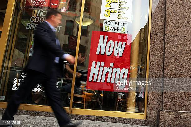 A man walks by a 'now hiring' sign in the window of a fast food restaurant on August 7 2012 in New York City In a further sign that the American...