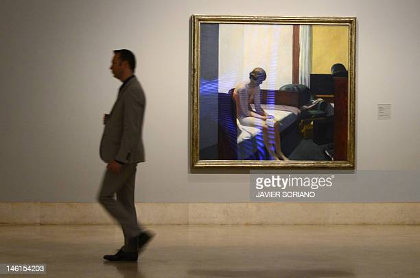 A man walks by a painting by US artist Edward Hopper entitled 'Hotel Room' at the ThyssenBornemisza Museum in Madrid on June 11 2012 AFP PHOTO/...