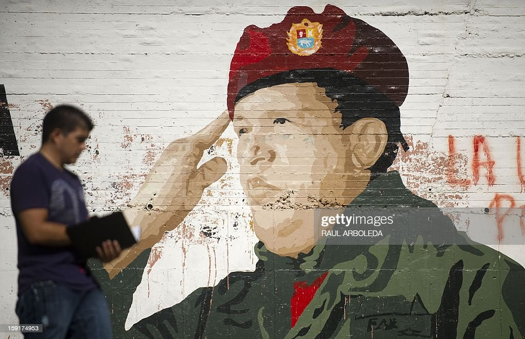 A man walks by a painting on a wall of Venezuelan President Hugo Chavez in Caracas on January 9, 2013. Venezuela's Supreme Court on Wednesday upheld the indefinite delay of Chavez's swearing-in to a new term and said his current administration can continue in office in the interim. Court president Luis Estella Morales read out the unanimous decision of the panel of seven magistrates who handle constitutional issues before the court. Chavez, who underwent his fourth round of cancer surgery in Havana nearly a month ago, is suffering from a severe pulmonary infection that has resulted in a respiratory insufficiency. AFP PHOTO/Raul ARBOLEDA