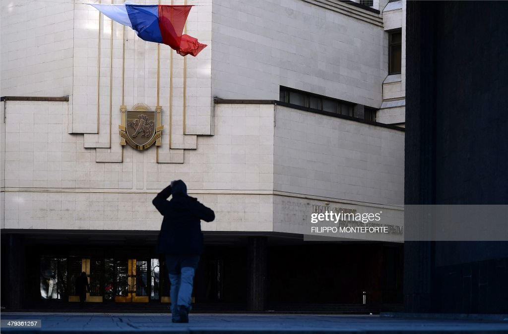 A man walks by a partially dismantled inscription written in the Ukranian language reading 'The Supreme Council of the Autonomous Republic of Crimea' on the Crimean parliament building in Simferopol, Crimea, on March 18, 2014. President Vladimir Putin has backed the approval of a draft agreement which would incorporate Ukraine's region of Crimea into Russian territory, according to an official instruction published today.