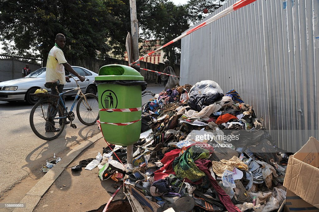 A man walks by a pile of abandoned shoes and clothing on January 2, 2013 in a street of Abidjian where at least 60 persons died in a stampede among crowds gathered for celebratory New Year's Eve fireworks that also left dozens injured. Ivory Coast began today three days of national mourning. AFP PHOTO / ISSOUF SANOGO