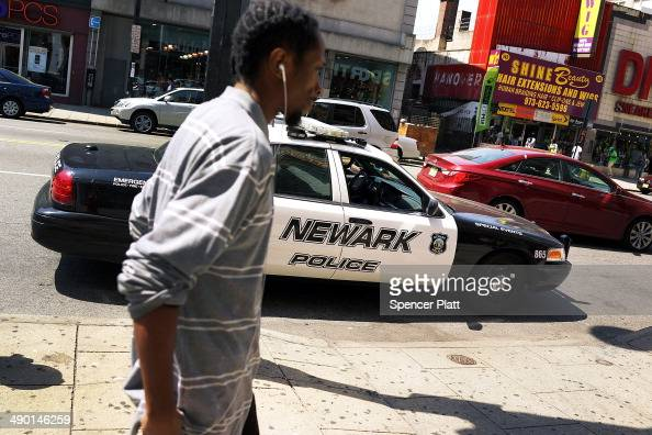 A man walks by a police car in downtown on May 13 2014 in Newark New Jersey Voters in New Jersey's largest city go to the polls on May 13 to choose a...