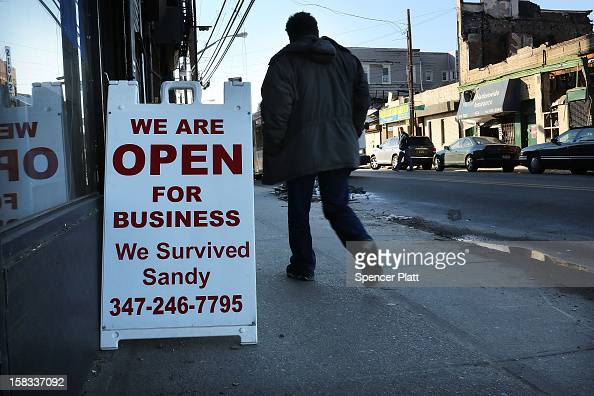 A man walks by a recently reopened business near the beach in Rockaway on December 13 2012 in New York City Much of the Rockaway neighborhood is...