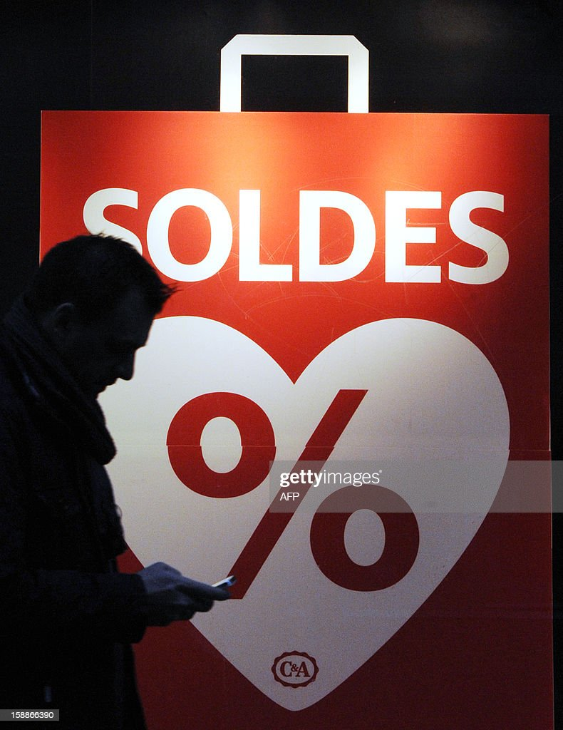 A man walks by a shopwindow bearing an advertisement reading 'Sales' in Metz, eastern France, on January 2, 2013 on the first day of the regional winter sales, one week ahead of national sales. AFP PHOTO JEAN-CHRISTOPHE VERHAEGEN