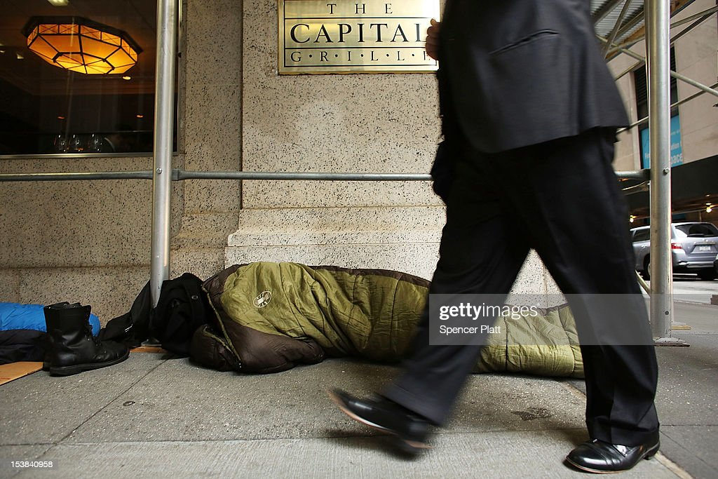 A man walks by a sleeping 'Occupy Wall Street' protester in the financial district in Manhattan on October 9, 2012 in New York City. State Comptroller Thomas DiNapoli will release his annual report on employment and earnings October 9, in New York' City's financial industry, one of the worlds largest. While employment is still down thousands of positions since the economic crisis of 2008, DiNapoli has said that last year the sector employed 166,600 people in hedge funds, investment banks and securities trading firms.