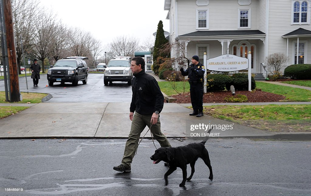 A man walks by Abraham L. Green and Son Funeral Home in Fairfield, Connecticut, December 17, 2012 as preparations take place for Noah Pozner,6 one of the victims of the elementary school shooting in Newtown, Connecticut. Funerals began Monday after the school massacre that took the lives of 20 small children and six staff, triggering new momentum for a change to America's gun culture. The first burials, held under raw, wet skies, were for two six-year-old boys who were among those shot in Sandy Hook Elementary School. On Tuesday, the first of the girls, also aged six, was due to be laid to rest. There were no Monday classes at all across Newtown, and the blood-soaked elementary school was to remain a closed crime scene indefinitely, authorities said. AFP PHOTO/Don Emmert