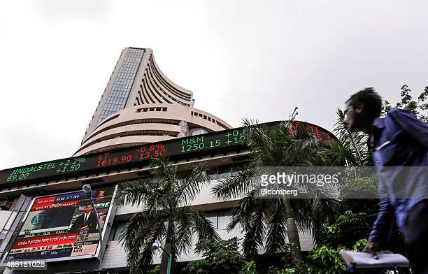 A man walks by an electronic ticker board that indicates stock figures at the Bombay Stock Exchange in Mumbai India on Tuesday Aug 25 2015 Indian...