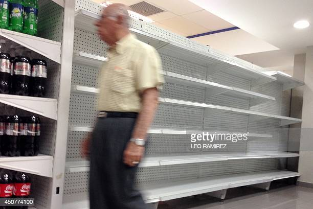 A man walks by an empty shelf inside a private market in Caracas on June 17 2014 Acetone hair colorants deodorant razors makeup and even coffins are...
