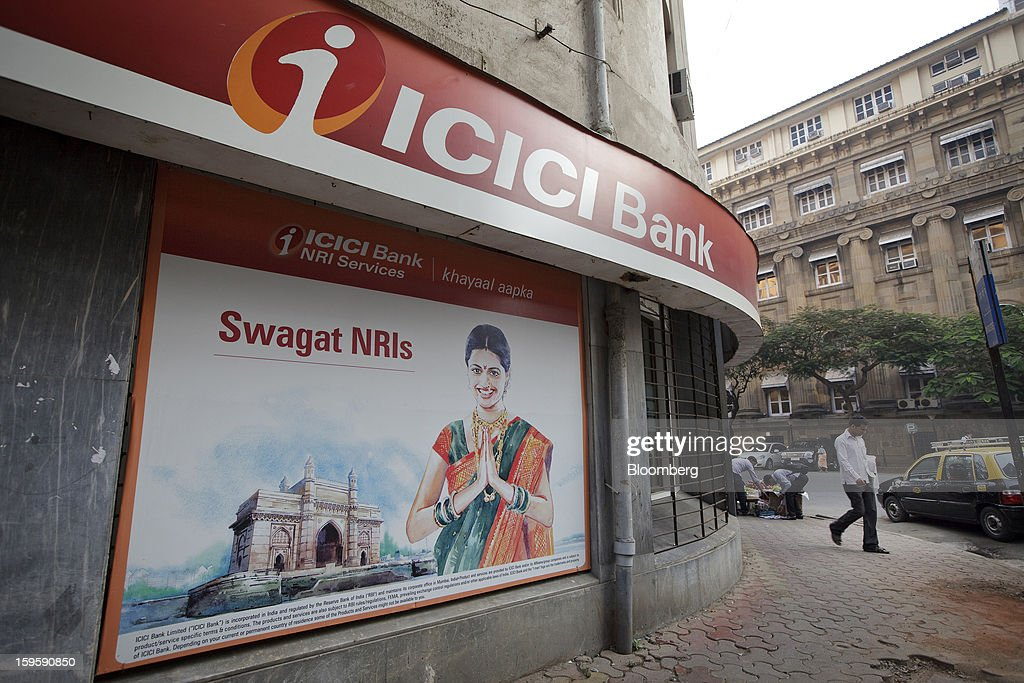 A man walks by an ICICI Bank Ltd. branch in Mumbai, India, on Wednesday, Jan. 16, 2013. India's financial system has been made vulnerable by a deterioration in bank assets and a lack of capital as the economy slowed, according to the International Monetary Fund. Photographer: Kuni Takahashi/Bloomberg via Getty Images