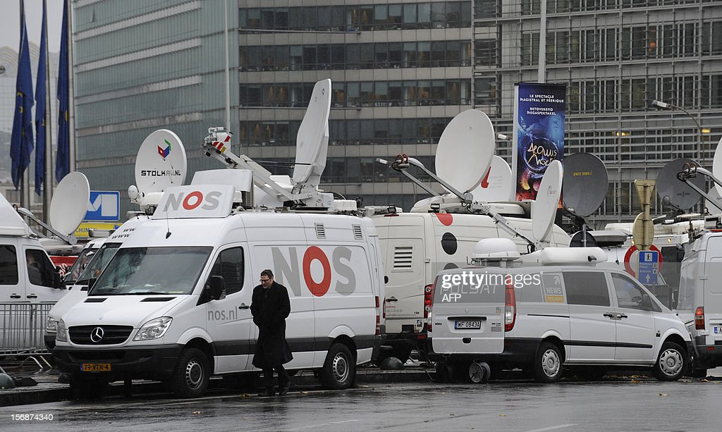 A man walks by broadcast trucks near the EU Headquarters on November 23, 2012 in Brussels, during a two-day European Union leaders summit called to agree a hotly-contested trillion-euro budget through 2020. European leaders voiced pessimism on reaching a deal on a trillion-euro EU bdget, as gruelling talks pushed into a second day with little prospect of bridging bitter divisions. AFP PHOTO / THIERRY CHARLIER