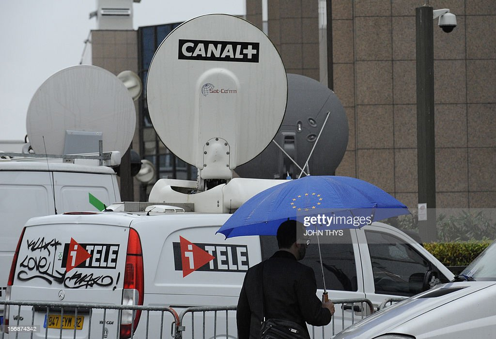 A man walks by broadcast trucks near the EU Headquarters on November 23, 2012 in Brussels, during a two-day European Union leaders summit called to agree a hotly-contested trillion-euro budget through 2020. European leaders voiced pessimism on reaching a deal on a trillion-euro EU bdget, as gruelling talks pushed into a second day with little prospect of bridging bitter divisions. AFP PHOTO / JOHN THYS