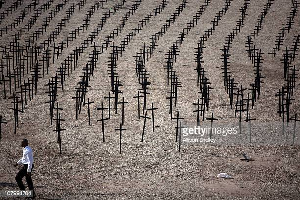 A man walks by crosses set up as a memorial in memory of the tens of thousands killed and buried in the mass grave at Titanyen on January 11 2011 on...
