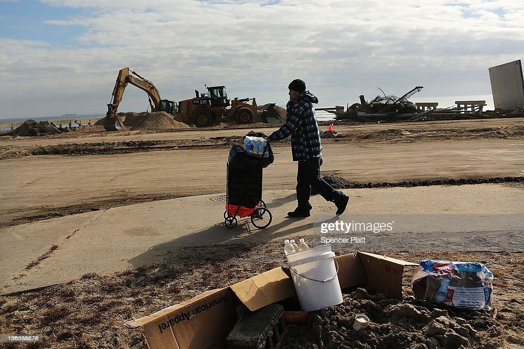 A man walks by debris in the heavily damaged Rockaway neighborhood where a large section of the iconic boardwalk was washed away on November 14, 2012 in the Queens borough of New York City. Two weeks after Superstorm Sandy slammed into parts of New York and New Jersey, thousands are still without power and heat.