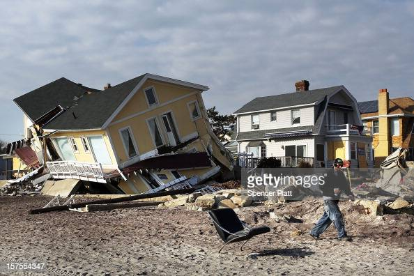 A man walks by destroyed homes along the beach December 4 2012 in the Rockaway neighborhood of the Queens borough of New York City New York Governor...