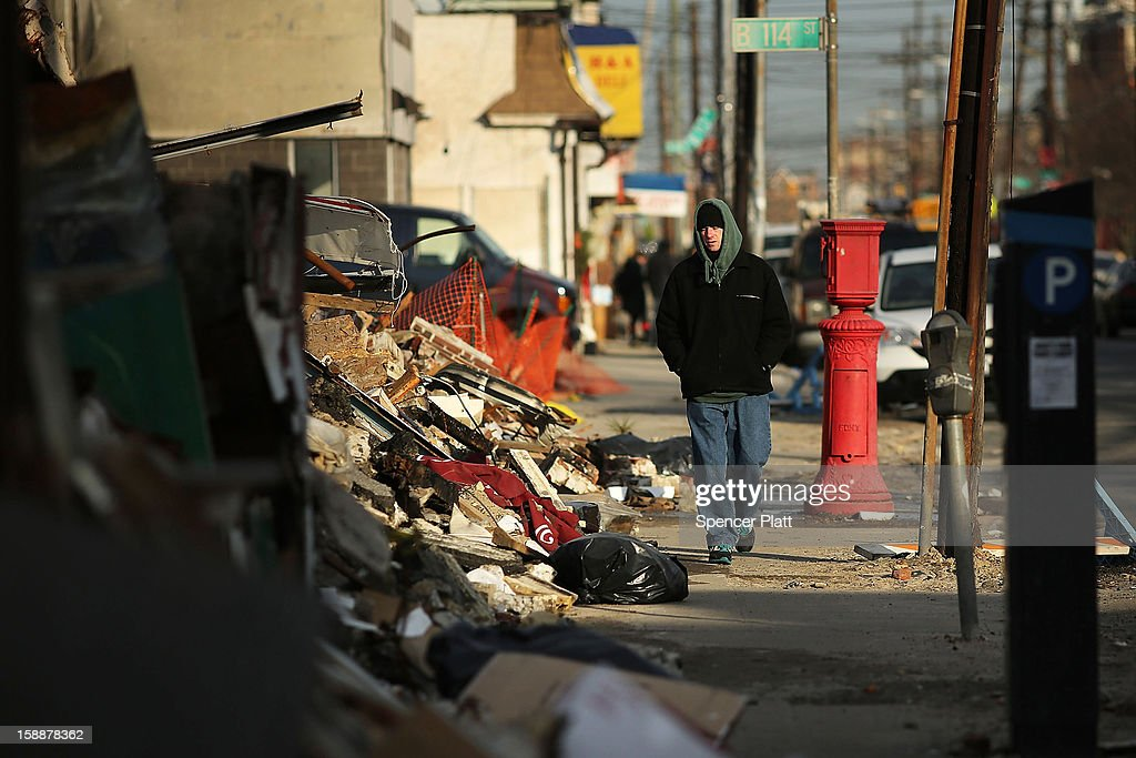 A man walks by destroyed homes and businesses after Superstorm Sandy in the Rockaways on January 2, 2013 in the Queens borough of New York City. Criticism, including by President Barack Obama, has been directed at the Republican House's decision to adjourn without passing a Superstorm Sandy aid bill. According to early estimates, Superstorm Sandy inflicted at least $50 to $60 billion in damage across the Northeast, making it one of the most destructive storms ever.