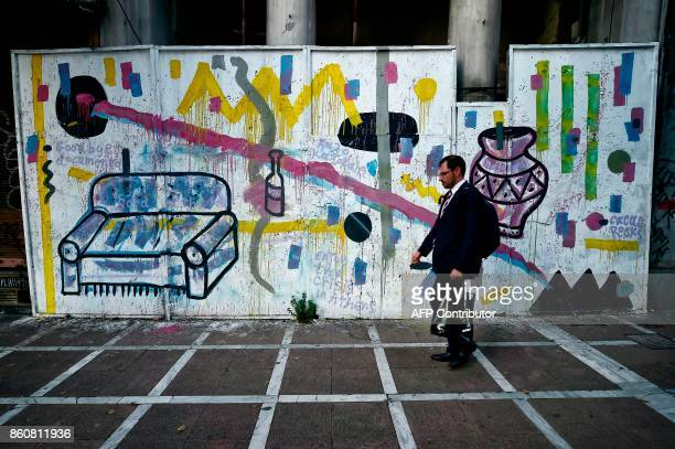 A man walks by graffiti by Greek street artist Cacao Rocks at an abandoned building in Athens on October 11 2017 An ongoing exhibition devoted to...